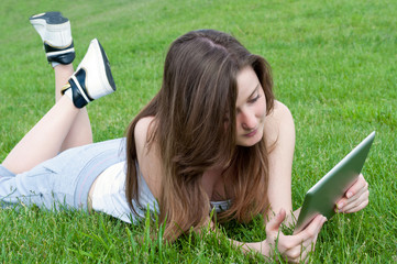 Girl with tablet on lawn.