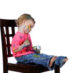 Toddler having fun sitting painting herself