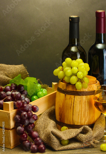 barrel, bottles and glasses of wine and ripe grapes