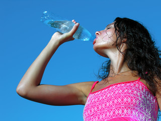 Young woman drinking cold water in hot day