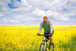 young man cycling in canola field