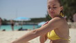 Woman on the beach applying sun block lotion, tracking shot