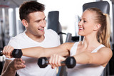 Trainer helping a woman work out with dumbbells