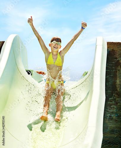 Leinwanddruck Bild Child on water slide at aquapark.