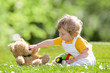 Kind mit Teddybär auf einer Sommer-Wiese