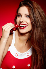 happy woman with cherries over red