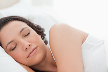 Close-up of a young woman sleeping in a bed