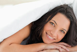 Attractive woman with green eyes under the duvet