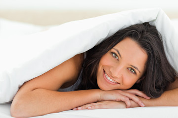 Woman with green eyes under the duvet