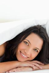 Green eyed woman under the duvet