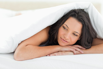 Cute young woman under the duvet