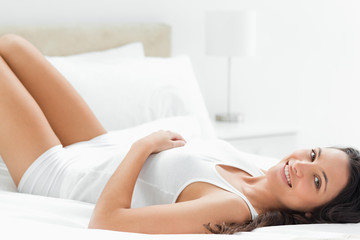 Delighted woman lying in her bed