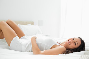 Pleasing smiling woman lying in her bed