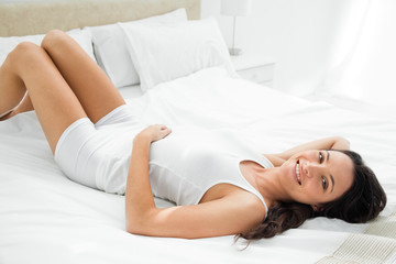 Pleasing woman lying in her bed