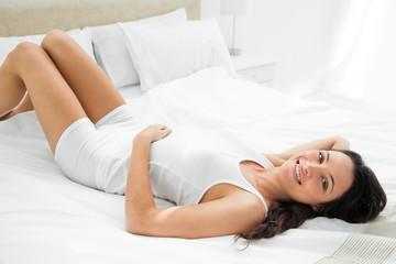 Pleasing woman lying in her bed