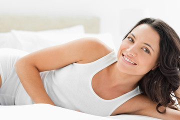 Adorable woman lying in white sheets