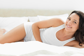 Charming woman lying on white sheets