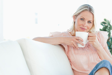Woman sitting on the sofa with a coffee in her hands