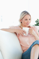 Beautiful blonde woman sitting on the sofa