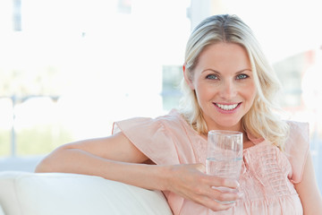 Blonde woman smiling at the camera while holding a glass