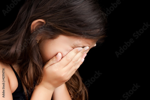 Portrait of a girl crying and hiding her face