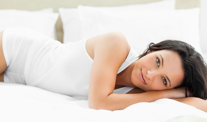 Pleasant woman lying on her bed
