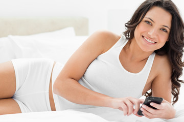 Close-up of a smiling brunette playing with her smartphone