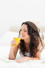 Attractive brunette drinking an orange juice