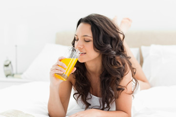 Attractive brunette drinking a fruit juice