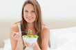 Young woman smiling while eating a salad