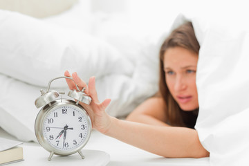 Woman in her bed turning off her alarm clock
