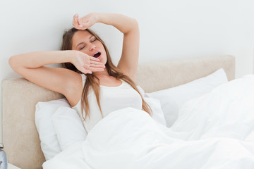 Beautiful woman yawning and stretching her arms