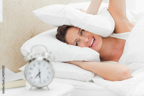 Woman crying while her alarm is ringing