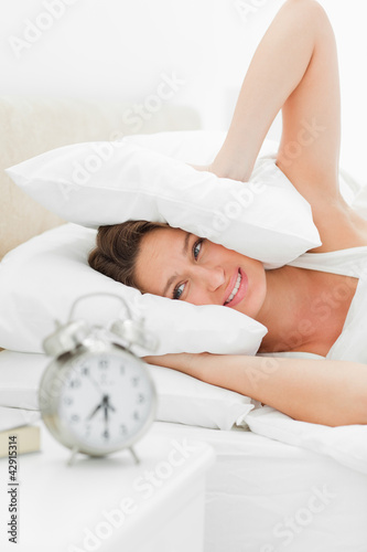 Woman crying while her alarm is ringing loudly