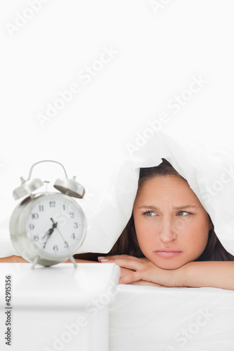 Woman sulking under her duvet while watching her alarm