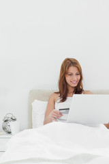 Close-up of a redheaded sitting on her bed while using her credit card online