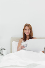 Woman sitting on her bed while using her credit card online