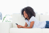 Cool brown woman texting while lying on her sofa