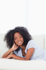 Portrait of a smiling fuzzy hair woman lying on her belly