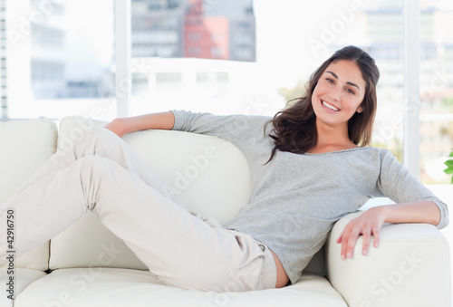 Portrait of a happy woman lying on her divan