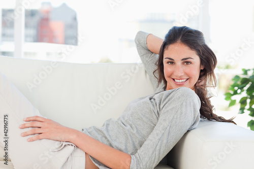 Portrait of a smiling beauty lying on her divan