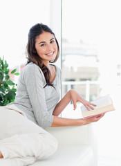 Portrait of a beaming brunette holding a novel