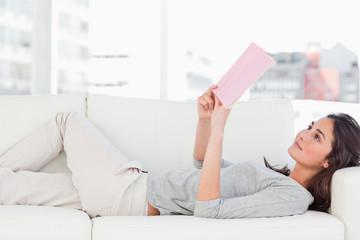 Smiling brunette lying on her sofa