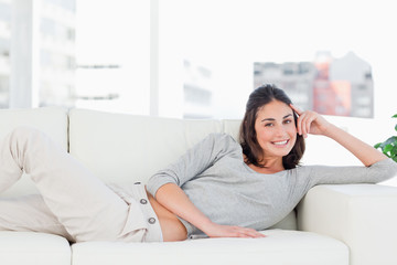Portrait of a happy brunette on her sofa