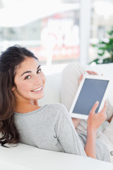 Portrait of a smiling brunette using a touchpad