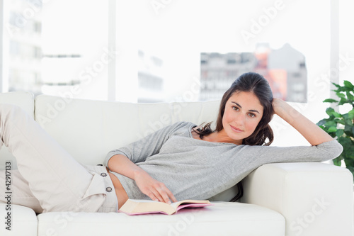 Portrait of a brunette reading on her sofa