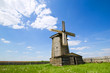 wooden windmill on the green field in Russian village