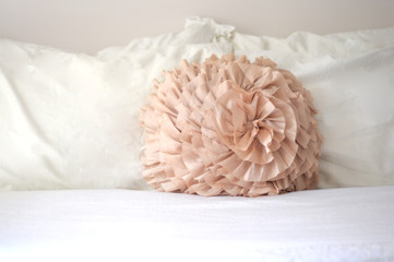 Pastel peach decorative pillow white sheets in bedroom