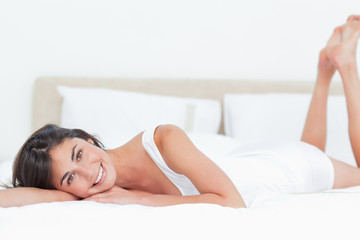 Portrait of a beautiful smiling brunette in her bed