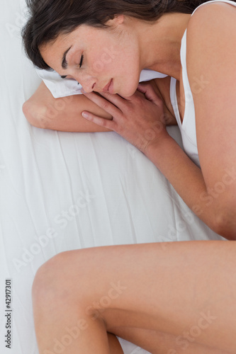 Close-up of a brunette sleeping in fetal position